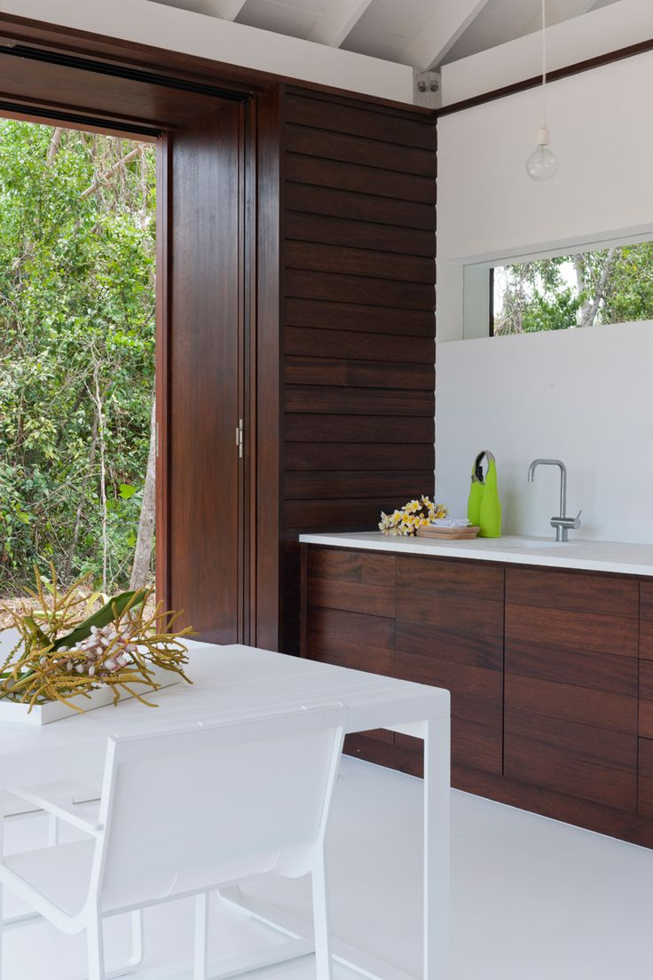Based on a remote tropical island in Far North Queensland, the one-bedroom house opens up completely so cooling breezes can flow through and residents can enjoy views of the nearby beach and surrounding tropical vegetation. The timber and stone used throughout complement the natural environment beautifully.  Architecture: Renato D'Ettorre Architects   Photographer: Willem Rethmeier  Products Selected: Scala and Monsoon collections available from Reece Bathrooms.