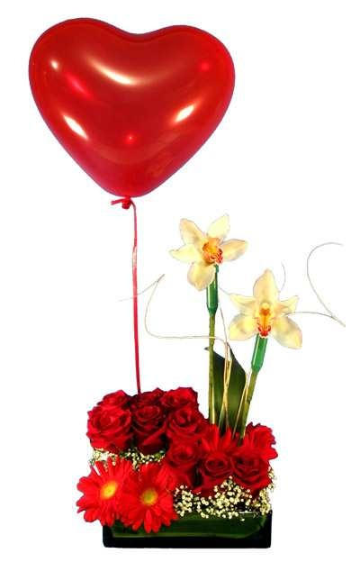 Original y elegante bandeja de cristal con rosas, gérberas, dúo de orquídeas y hermoso globito con helio.