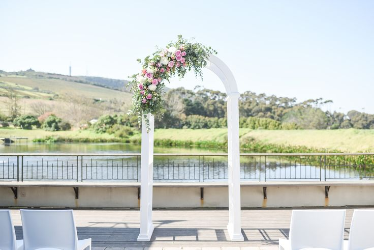 White wooden arch with greenery and pastel colour flower arrangement