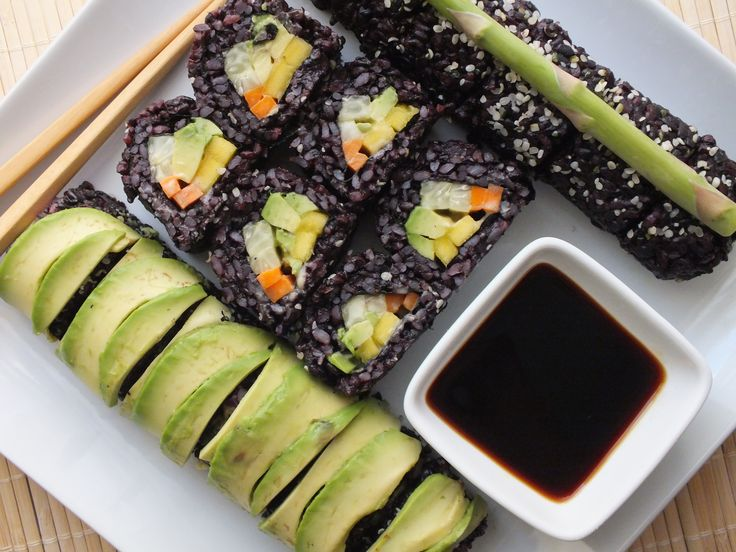 Colorful black rice vegan  gluten-free sushi, made with: black rice, nori, cucumber, asparagus, avocados, daikon, carrot, mango, red cabbage, yellow bell pepper, and a tamari ginger sauce.