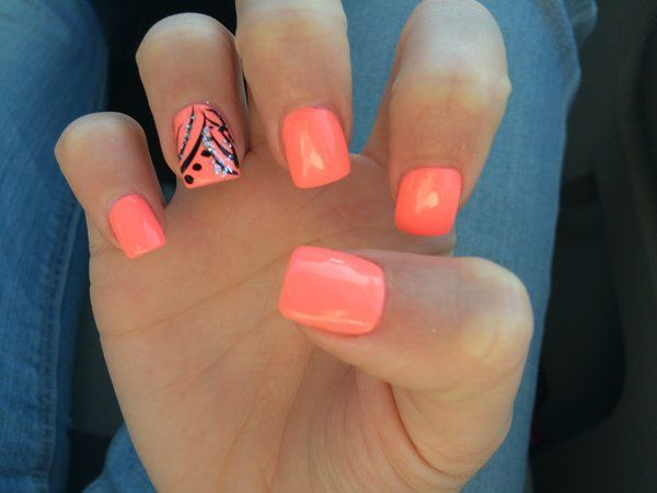 Peach nails with a black and silver design on the ring finger.