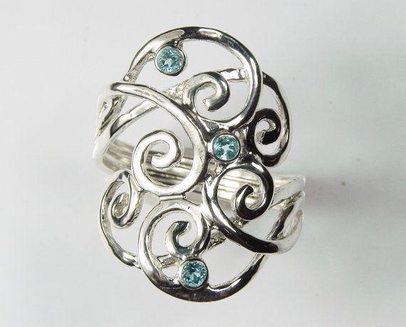 Een blauw topaas ring met golven en wervelingen van sterling zilver lappen rond mooie weinig sprankelende winter blauw ijs edelstenen. Dit is mijn unieke handgemaakte zilveren swirl ring, met spiralen van golven wervelende zoals ze wikkel rond uw vinger. Met mousserende glinsterende swiss blauwe topaas edelstenen die doet denken aan de kleuren van de Caribische zee en de hemel. Drie, 2.5mm faceted edelstenen zijn verscholen in de wervelingen en glinsteren tussen de golven van sterling…