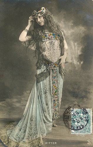 Boheme. photo, figure, woman, front, 3/4 view, holding, holding high, looking back, vintage, ethnic, happy
