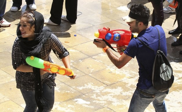 """In this picture taken on Friday, July 29, Iranian youths shoot water to each other with their water guns, during water fights at the Water and Fire Park in northern Tehran, Iran. Iran is trying to put down a new wave of civil disobedience - flash mobs of young people who break into boisterous fights with water guns in public parks. A group of water fighters was arrested over the weekend, and a top judiciary official warned Monday that """"counter-revolutionaries"""" were behind them. Throughout…"""
