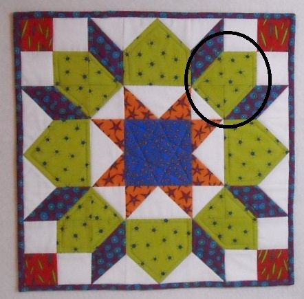 """Blogger: """"After making this mini quilt, I realized I could make the area I have circled below better.  I'm not crazy about all those seams in that area so I eliminated them and wrote a tutorial which is posted below the photo."""""""