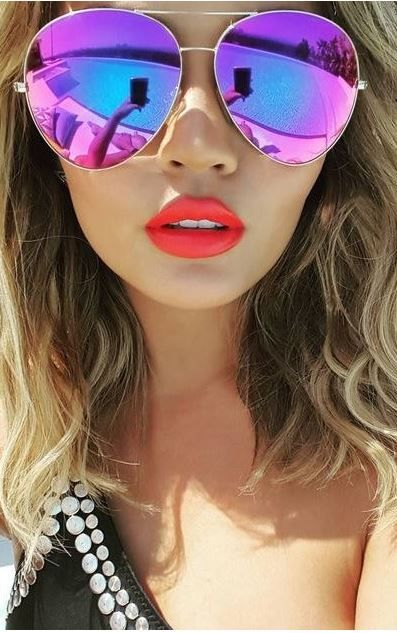 Who made Chrissy Teigens black one shoulder swimwear and purple aviator sunglasses?
