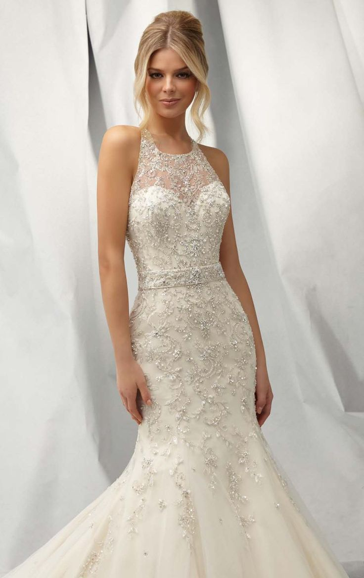 Look absolutely stunning in Angelina Faccenda by Mori Lee 1301. This sophisticated net wedding gown features a sheer haltered neckline. The fitted bodice with lace back design perfectly flaunts your upper body curve that will make you look amazing. A full length mermaid skirt flares down the floor to complete a charming look.
