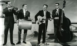 Lonnie Donegan plays guitar with his band in 1958.