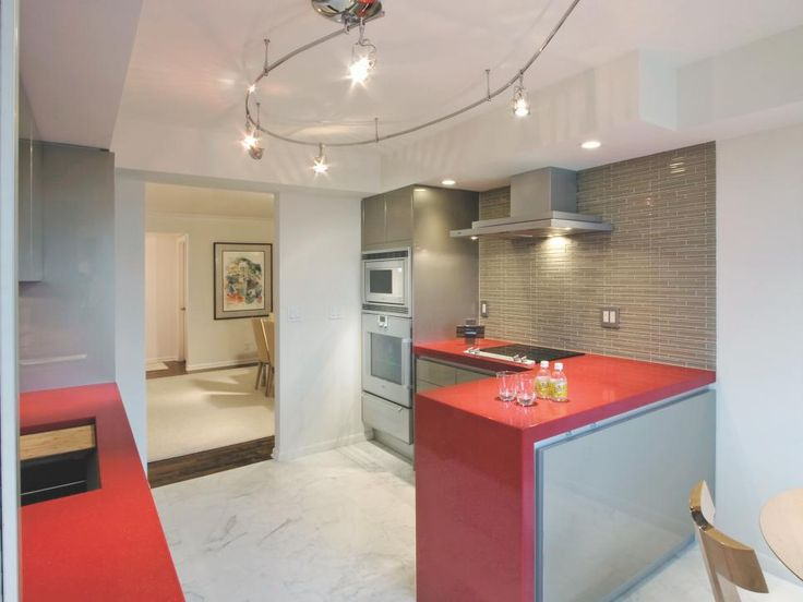 A red quartz countertop was at the core of this retired couple's wishes for their city condominium. Highlighting their art collection was achieved with extensive lighting on independent controls. Appliances behind panels or an aluminum finish were the solution to the homeowners' desire to avoid stainless steel. Calcutta gold marble for the floor and horizontal glass tile on the backsplash in a mix of matte and gloss finish were chosen to coordinate with the acrylic-finished European…