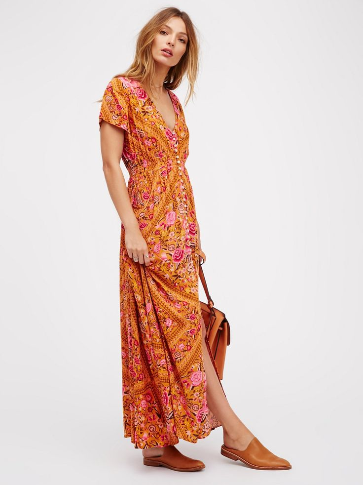 Babushka Gown | Flowy maxi gown with a gorgeous garden and tribal-inspired mixed print. Features a V-neckline, shell buttons down the front and a stretchy smocked band around the waist for a comfortable fit. High center slit. Hidden side pockets.