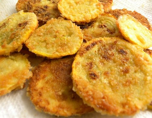 Summer Fave. Fried squash. 2-3 yellow squash (zucchini works too) canola oil for frying, cracker crumbs (about 1 sleeve of saltine crackers crushed), 2 eggs,  1-2 tablespoons milk  1. Slice the squash to about 1/4″ thick. 2. Whisk the 2 eggs and the milk together. 3. Dip the squash slices in the egg mixture, then in the cracker crumbs. I usually crumb one squash at a time. One squash will usually fill my skille