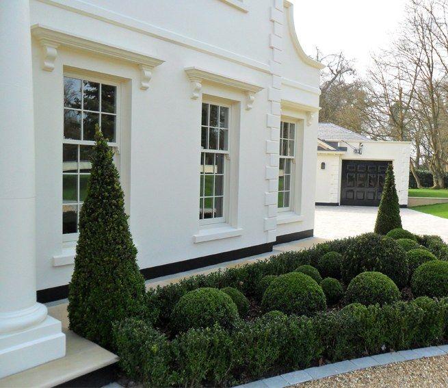 Stucco, high gloss black garage doors, clean landscape