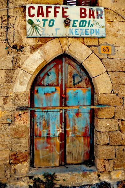 Good Cheer - A beautiful dilapidated wooden door and an old faded sign of a closed-down coffee shop in the Old Town of Rhodes.