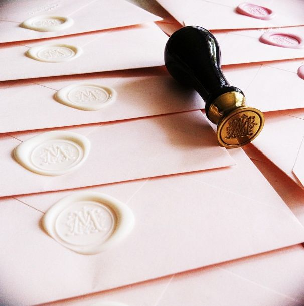 Create this with stomp stamps wax seal http://www.notonthehighstreet.com/stompstamps/product/monogram-initial-wax-seal