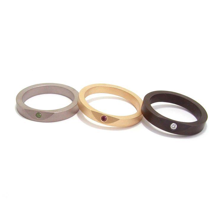 'Less Is More' ringen, titanium met groene diamant, gematteerd geelgoud met paarse diamant en zirkonium met witte diamant.