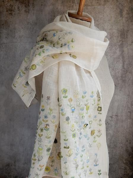 Light ecru linen embroidered with flowers on the hems of the scarf. About 20 x 54 inches.