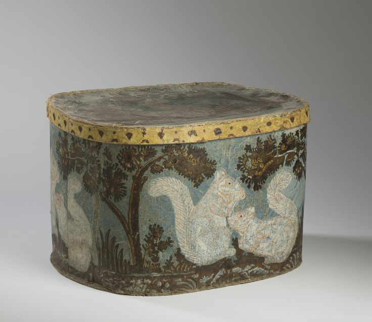 """LARGE HAT BOX WITH SQUIRREL MOTIF AND BLUE GROUND. Height 13 inches, length 19 ½ inches. Provenance: Northeast Auctions, July 31, 2009, lot 468 Literature: Lilian Baker Carlisle, """"Hat Boxes and Bandboxes at Shelburne Museum, p. 33 Est. $700-$1,000"""