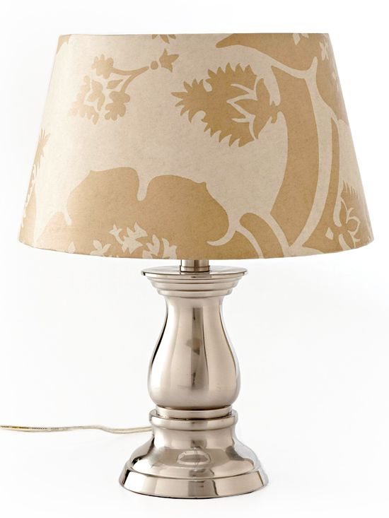 """To cover a lampshade, place a piece of wallpaper on a flat surface. Roll the shade along the wallpaper, tracing both edges. Add 1/2"""" to each edge, cut out the cover, use spray adhesive to attach it. Snip the excess paper at even intervals, fold to the back of the shade and secure with spray adhesive."""