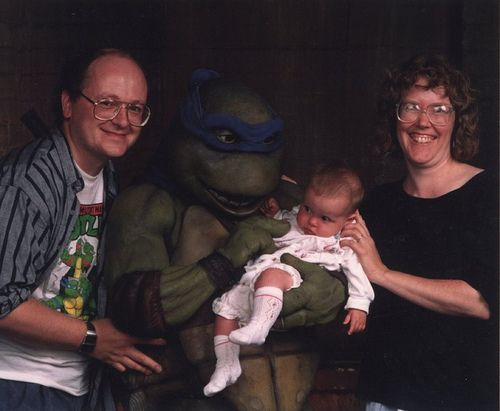 """Leonardo & the Peter Laird Family """"This is one of my all-time favorite photos. It was taken on the set of the first TMNT movie, down in North Carolina. My wife and I had brought our baby daughter with us on a visit to the set. The studio wanted to do some promotional photos of me and Kevin. After the photo shoot was done, we prevailed upon the photographer and the man in the Turtle suit to pose for a couple of shots with us and baby Em. I love the look Em is giving the Turtle!"""""""