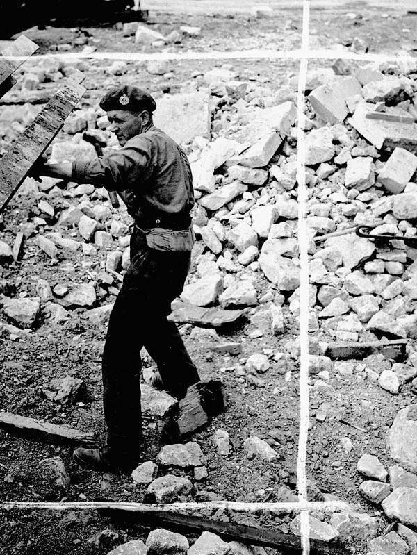 Sapper E.F. Dombrowski, 6th Field Company, Royal Canadian Engineers (R.C.E.), strips a steel beam from a damaged building to be used in constructing temporary bridges, Bretteville, France, 23 June 1944. Photographer: Frank L. Dubervill