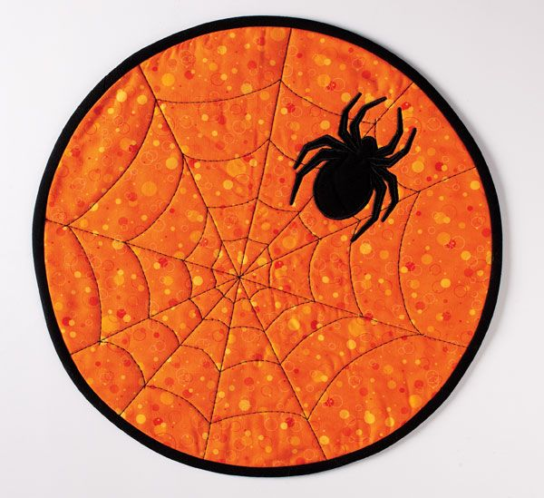 "This festive table accessory features a spooky black spider on an orange background and a web quilting design. Make a spooky placemat (14"") or a mug mat (7½"") size. Digital pattern available! #MugMat #Halloween #Decoration"
