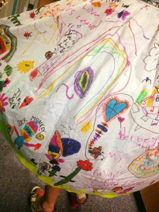 teacher wears dress made of kids art work