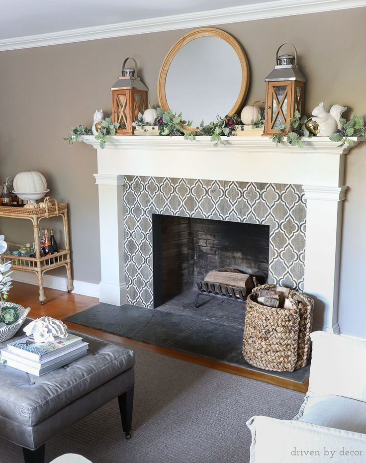 Fireplace decorated for fall with twin lanterns