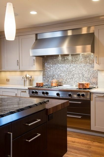 The 60-inch BlueStar range is backed by a field of stainless steel penny round tiles. The backsplash on either side is covered with 6- by 12-inch glass subway tiles from Architectural Ceramics.