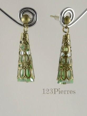 Boucles d'oreilles en cône de cristal irisé vert recouvert d'une dentelle métallique bronze. Ces boucles d'oreilles sont proposées avec des clous pour oreilles percées.  Cr - 16675972