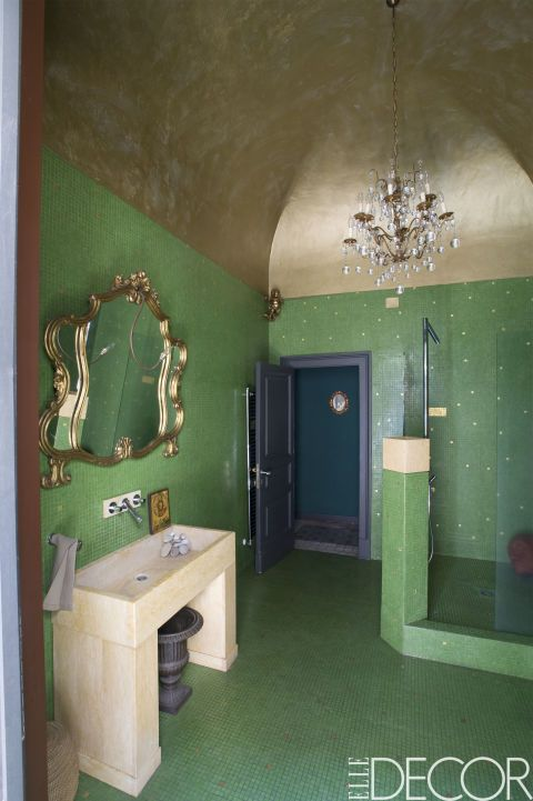 In a 19th-century Sicilian apartment, the walls and floor of the master bath are covered in jade green Bisazza tiles. The gold-leaf ceiling and grand chandelier add to the detailed aesthetic worthy of royalty.