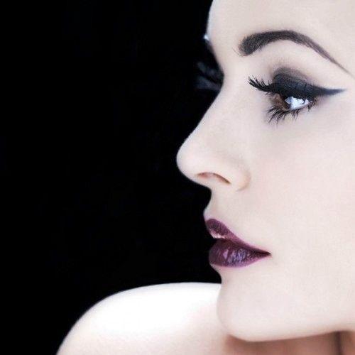 Elegant. Pale skin,black winged eyeshadow and deep purple lips.