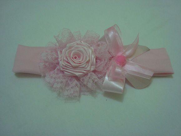 Faixa infantil em malha com elastano, flor em fita decorada em bico e laço duplo. A circunferência total da faixa mede 36 cm. R$ 14,90