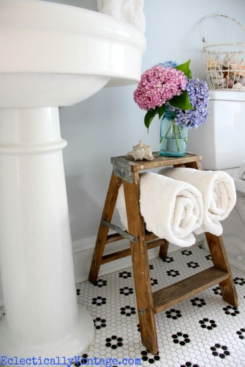 Cute towel storage in this bathroom - use an old stepladder! Love the floor and fun accessories like the metal basket from HomeGoods filled with seashells. eclecticallyvintage.com sponsored pin