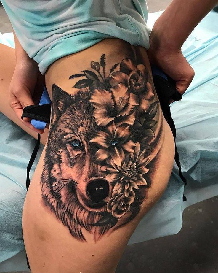 Kräftige Wolfs- und Blumentattoos am Oberschenkel