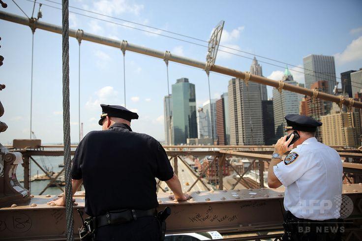 米国旗が白い旗にすり替えられたニューヨーク(New York)のブルックリン橋(Brooklyn Bridge)で、警備にあたる警察官(2014年7月22日撮影)。(c)AFP/Getty Images/Spencer Platt ▼14Aug2014AFP|米ブルックリン橋の白い旗、独アーティストが関与認める http://www.afpbb.com/articles/-/3023078 #Brooklyn_Bridge
