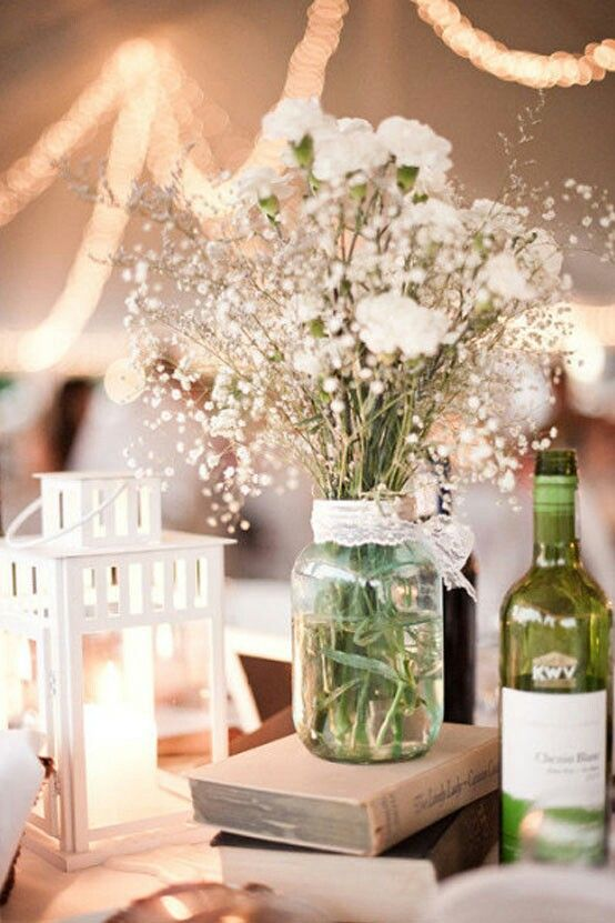 Centro de mesa de flores, libros y frascos
