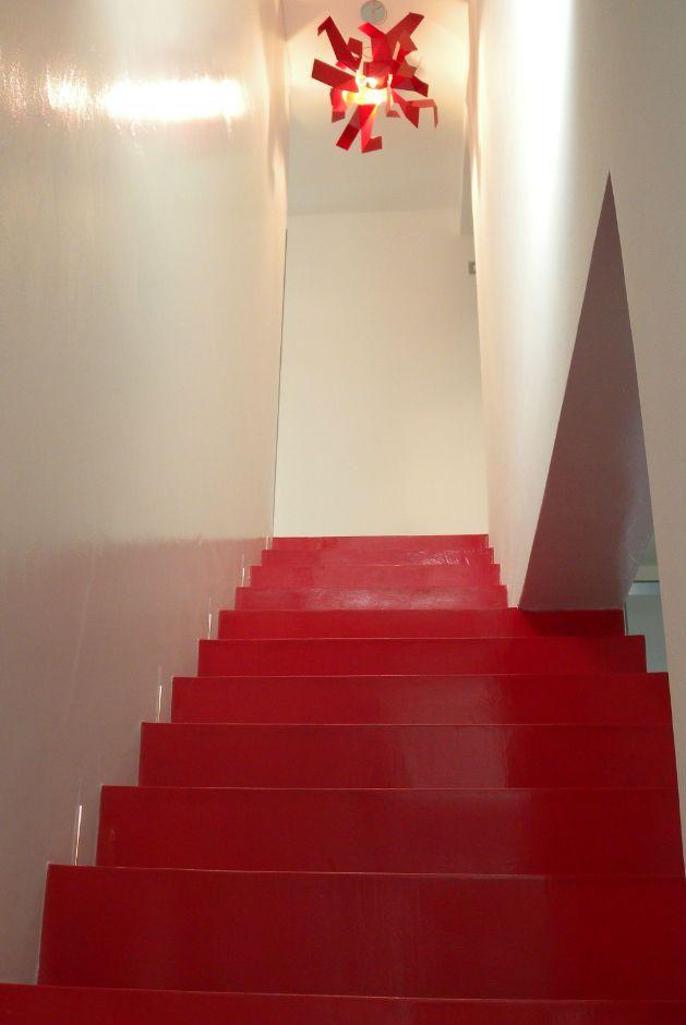 Rivestimento in resina rosso per la scala protagonista in un ambiente minimal.