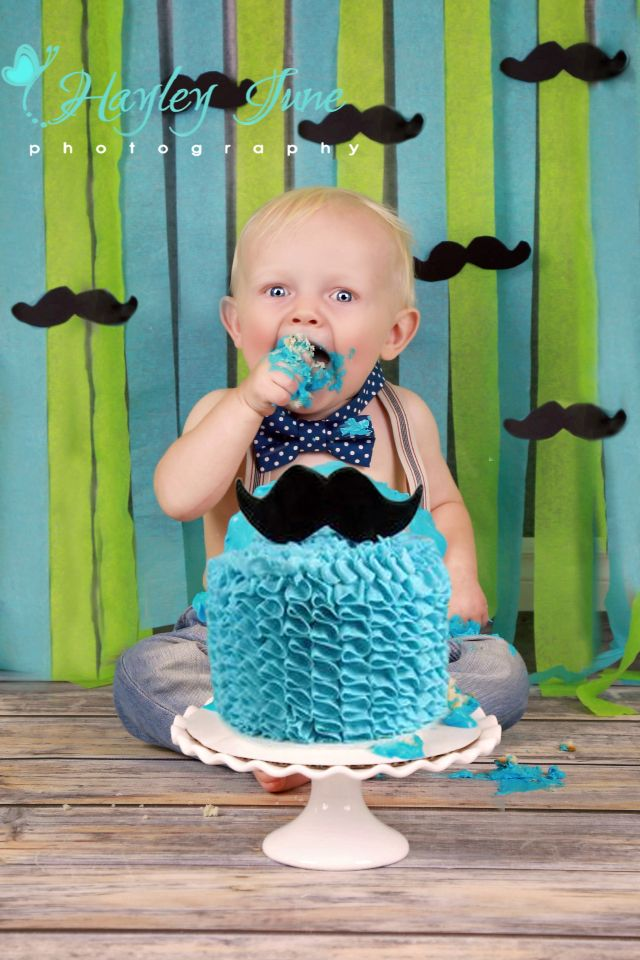 """Little man J is turning 1!  This little guy was so fun and had a great time smashing into his cake.  Our theme was blue, green and silver/grey """"little man mustaches and bow ties.""""   Calgary photo, cake smash, mustache birthday, first birthday picture photo, boy cake smash, Calgary cake smash photo"""