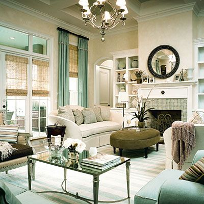 living rooms - French Mirrored Coffee Table gray green oval velvet ottoman white sofas black mirror blue green glass tiles fireplace chandelier seafoam green silk drapes bamboo roman shades window treatments blue white striped rug built-ins seafoam green velvet chairs