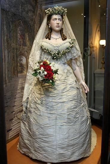 Queen Alexandra's 1863 wedding gown on display.  Like her mother-in-law Queen Victoria, Alexandra also had her lace frills removed for reuse, and it appears that the skirt of the gown has been altered into a more narrow shape than the fashionable bell shape of 1863.  The bodice however, is unaltered.