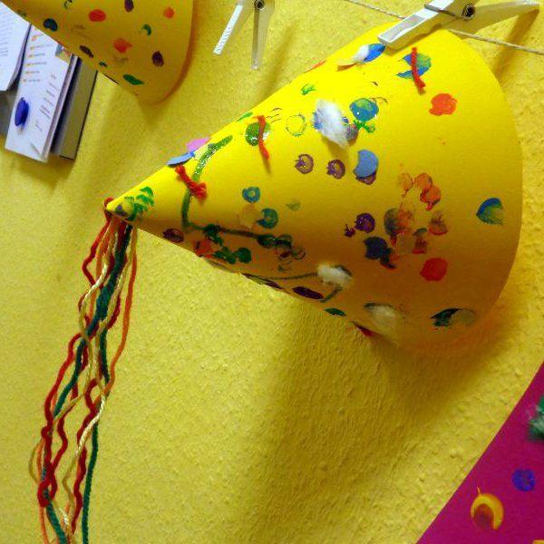 Die Krippe dekoriert ihre Gruppenräume zu Fasching mit selbst gemachten Masken, Hüten, Girlanden und Konfetti. Mit den kleinen Kindern unter drei Jahren basteln wir seit ein paar Tagen bunte Dekoration.