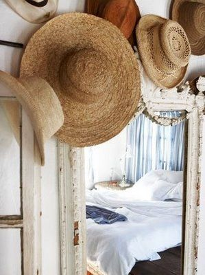 Love this casual display of straw hats in a summer bedroom.... saw this in Country Living Magazine and I'm going to do it around my mirror with my hats.
