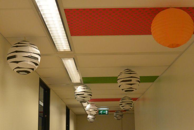 Lelijk systeemplafond opgevrolijkt met rijstpapieren ballonnen en stof.
