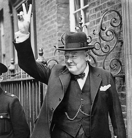 Winston Churchill in one of his iconic images, flashing the V for Victory sign