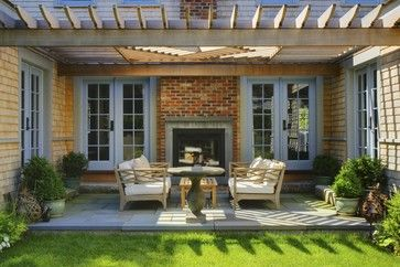 Fireplace flanked by double doors, stone patio, and trellis - www.skylarshomeandpatio.com #stone #patio