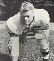 1954. Posed photograph of Chuck Noll in a football uniform without a helmet in a three-point stance. Played LB &G for the Cleveland Browns 1953-1959
