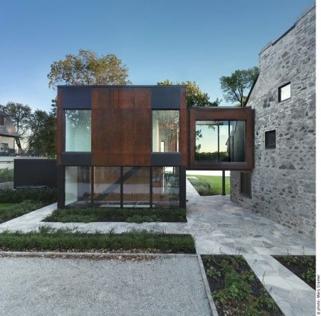 A 200-year-old stone house in Canada gets a striking metal-clad addition in this project by Henri Cleinge. The stark transition between old and new is meant to express the passage of time, the new volume representing the modern-day family and the old representing their ancestors.
