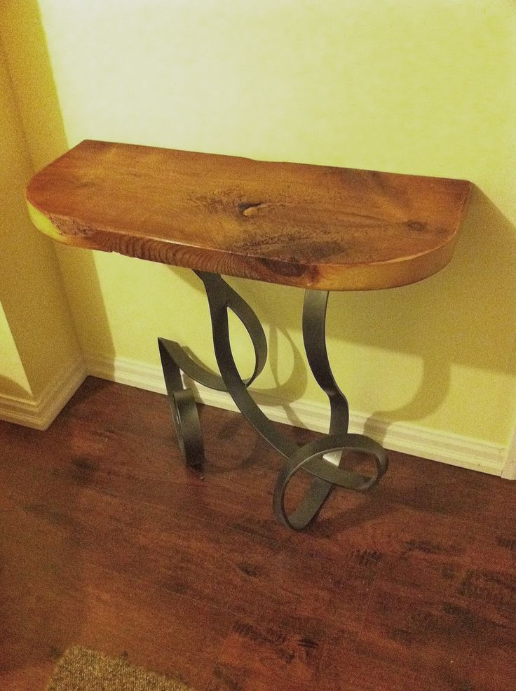 Custom console table made using reclaimed wood. Wrought iron base.