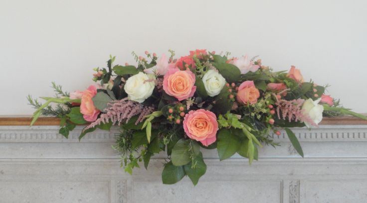 Top table/mantle arrangement of Miss Piggy Roses, Avalanche Roses, Pink Pop Roses, Coral Gladioli, Coral Hypericum, Ivory Astilbe and Berried Ivy.