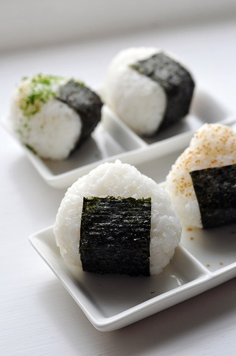 Japanese Cuisine: Onigiri [Rice ball with filling of pickled umeboshi (dried plum/apricot), salted salmon, katsuobushi (dried, fermented & smoked skipjack tuna), kombu (edible kelp) or tarako (salted pollock roe), and wrapped in nori (seaweed)].
